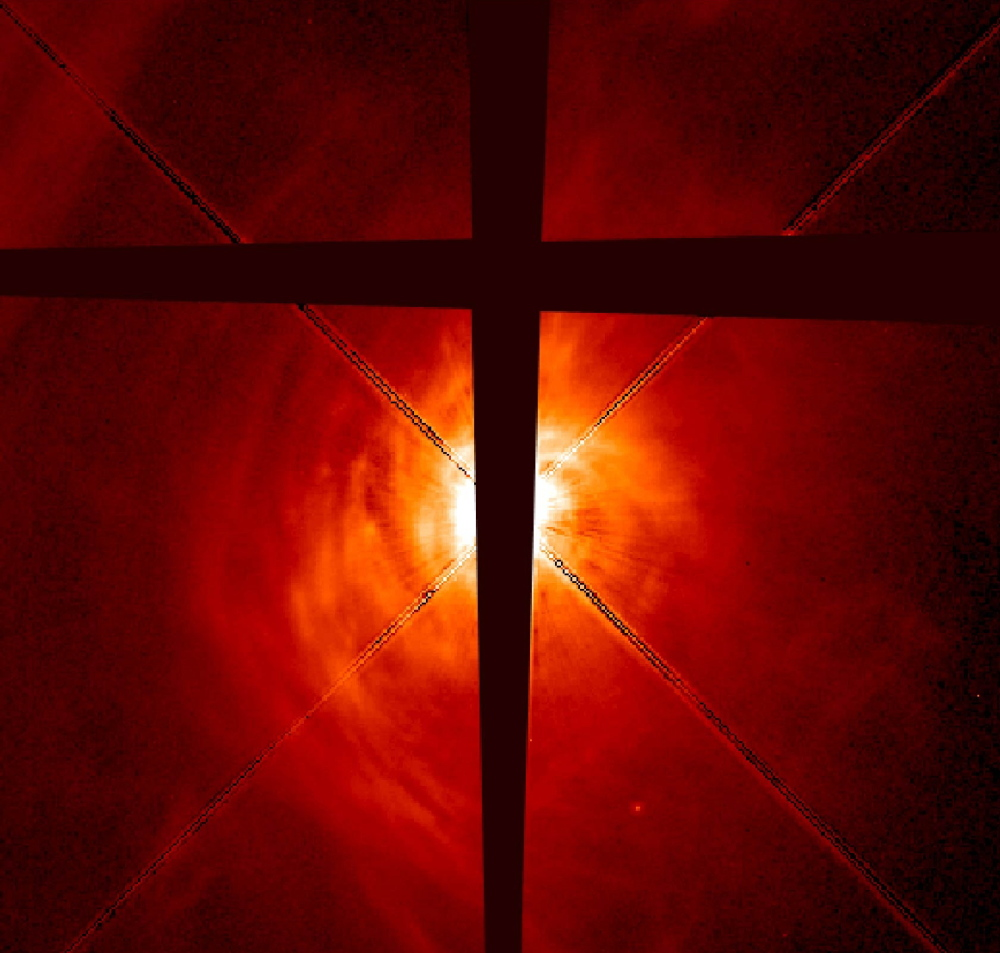 The developing star AB Aurigae has a swirling disk of dust and gas that includes clumps thought to be the beginnings of planet formation. The dark lines in the photo are made by an occulting bar on the telescope that cuts the glare from the star and makes the potentially planet-forming disk more visible. Some astronomers think that almost all stars in our galaxy have planets.