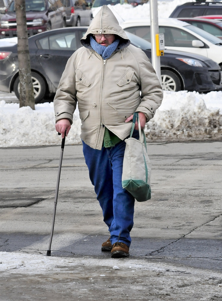 "Staff photo by David Leaming Dale Rollins bundled up to walk in the bitter cold in Waterville on Wednesday. ""I've had enough of this cold,"" Rollins said."