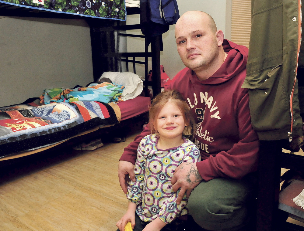 Richard Walsh and his children, Autumn and Aiden, sleeping in bed, in the room they share at the Mid-Maine Homeless Shelter in Waterville on Wednesday.