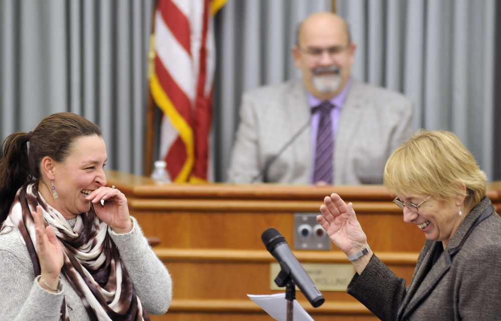 Deborah Towle, left, laughs Thursday with Attorney General Janet Mills while being sworn into the Augusta School Board at City Center in Augusta.
