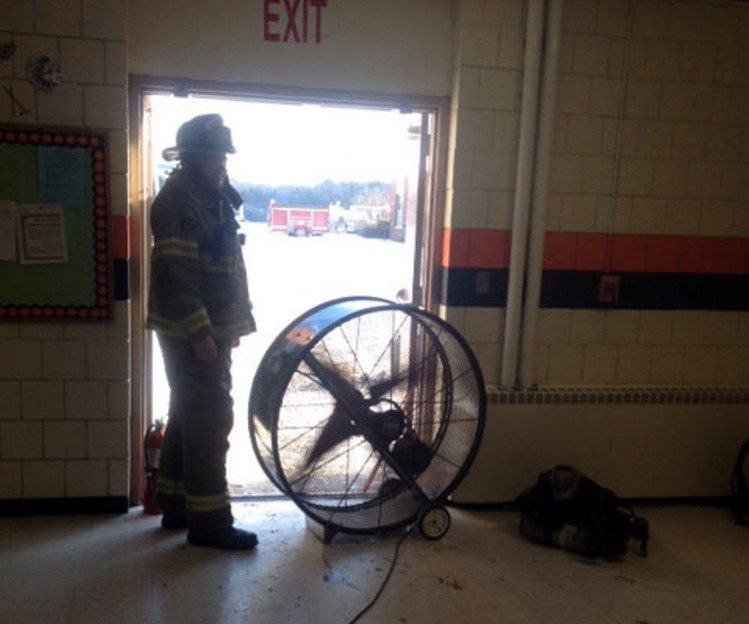 Skowhegan fire Lt. Matthew Quinn sets up a fan to clear smoke from Skowhegan Area High School after a bathroom fire Friday afternoon