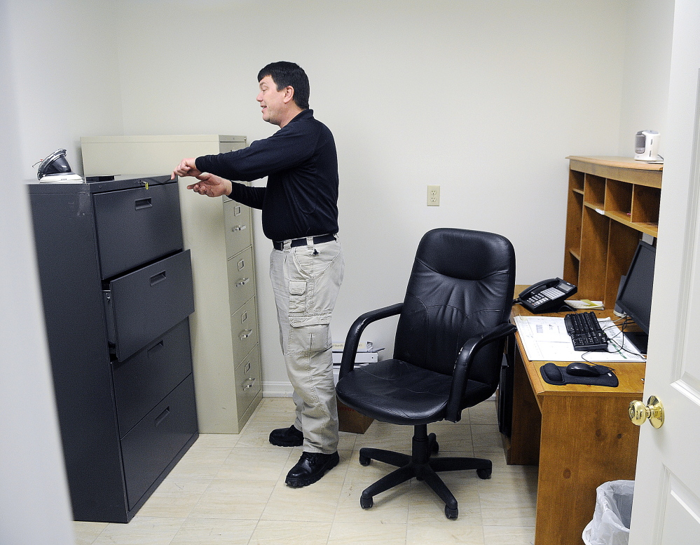 Monmouth Police Chief Kevin Mulherin arranges his office Thursday at the department's new station in Monmouth.