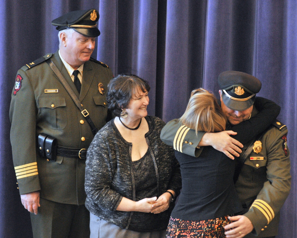 New Marine Patrol Col. Jon Cornish, right, hugs his daughter Katrina Cornish after she pinned his badge on him during a change of command ceremony on Friday at the Maine Criminal Justice Academy in Vassalboro. Retiring Marine Patrol Col. Joe Fessenden, left, and Cornish's wife, Kim Cornish, also attended the ceremony.