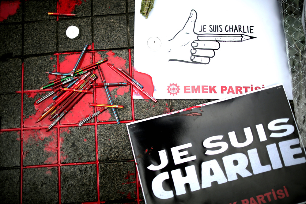"Broken pens and placards that read: ""I am Charlie"" lay on the ground as members of a leftist party gather outside the French consulate to pay tribute to the victims of the French satirical newspaper Charlie Hebdo, in Istanbul, Turkey, Friday."