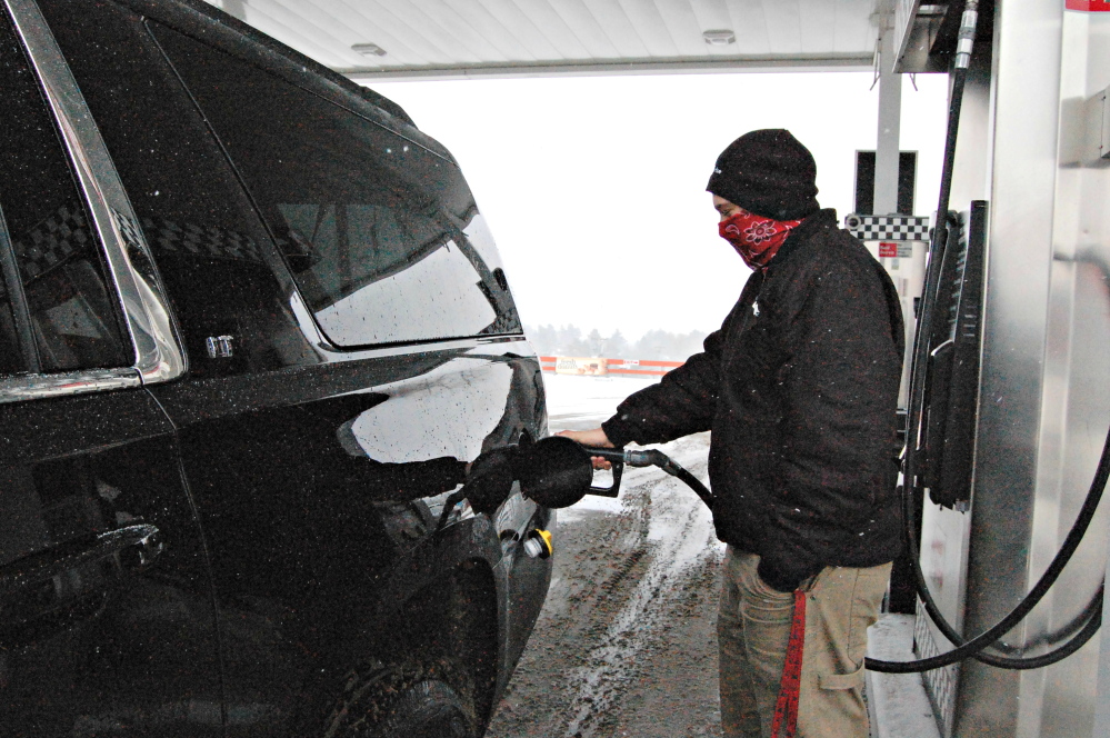 Zackary Grote, a business major at Thomas College in Waterville, attempts to stay warm while fueling up Friday at J&S Express Stop on Kennedy Memorial Drive in Waterville.