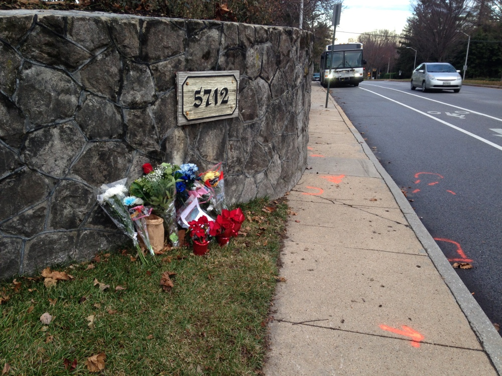 In this Dec. 29, 2014 file photo, flowers and messages are placed at the scene of a fatal collision between a car and bicyclist along a Baltimore residential street with a bike lane.