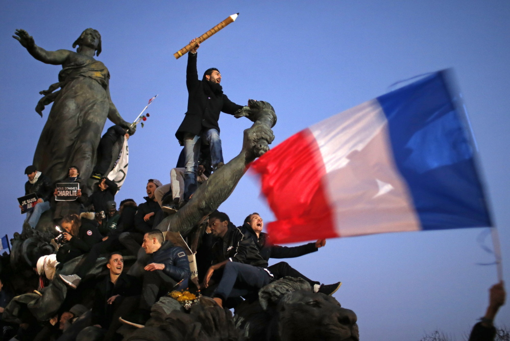 Some marchers carried France's flag and others held giant pens or pencils in a tribute to the cartoonists killed in the attack on the satirical French newspaper Charlie Hebdo.