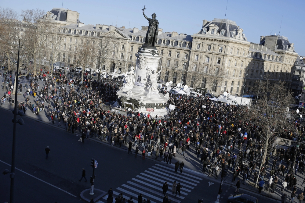 People start gathering at Republique square before the demonstration, in Paris on Sunday. A rally of defiance and sorrow, protected by an unparalleled level of security, on Sunday will honor the 17 victims of three days of bloodshed in Paris that left France on alert for more violence.