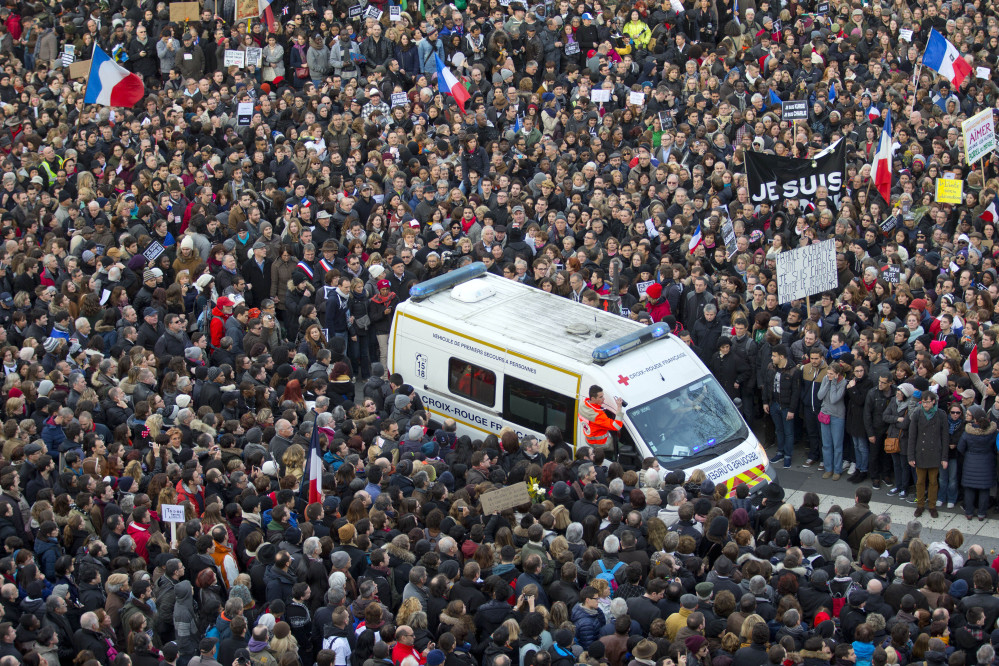 An ambulance makes its way as thousands of people gather at Republique square in Paris, France, Sunday, Jan. 11, 2015.  Thousands of people began filling France's iconic Republique plaza, and world leaders converged on Paris in a rally of defiance and sorrow on Sunday to honor the 17 victims of three days of bloodshed that left France on alert for more violence. (AP Photo/Peter Dejong)