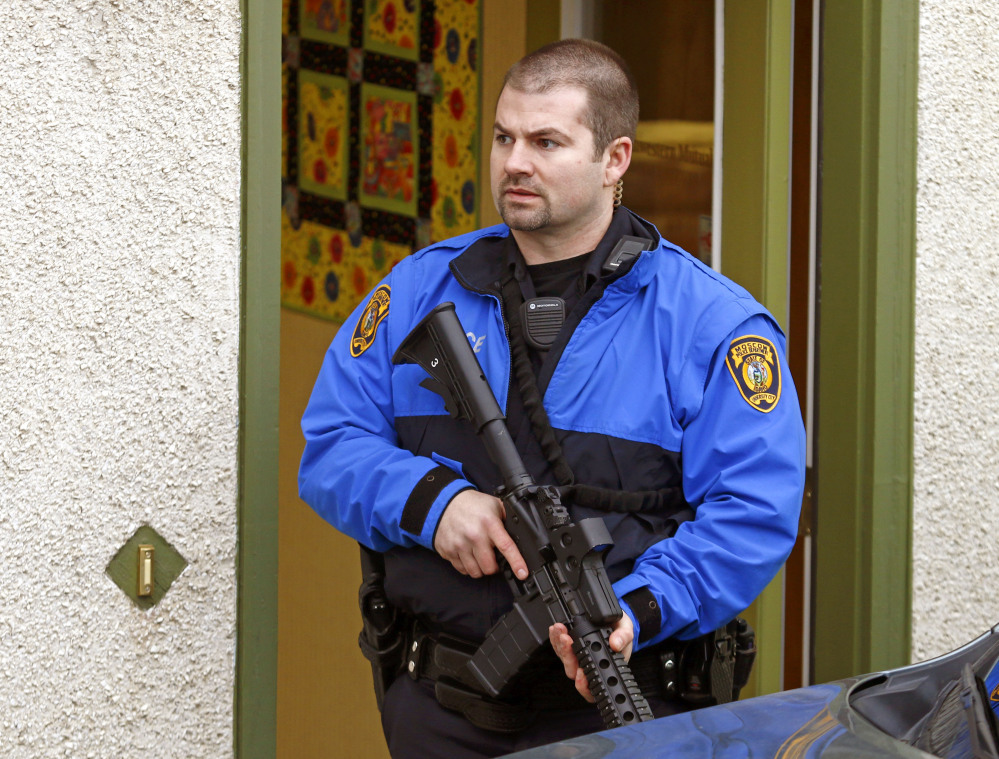 A police officers stands outside an office where two men were shot in Moscow, Idaho, on Saturday. Police say a gunman killed three people and critically wounded another during a spree at three locations in Moscow, Idaho.