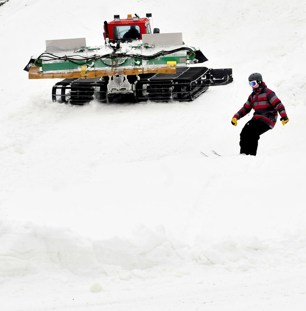 Nicholas Morris, of Canaan, skis over a small jump as Eaton Mountain Ski and Snowtubing company owner Dave Beers grooms trails on Sunday.