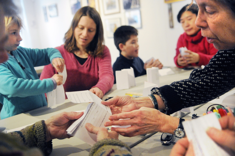 Margo Ogden, right, demonstrates how to fold paper into books during a bookmaking class at Harlow Gallery in Hallowell on Sunday