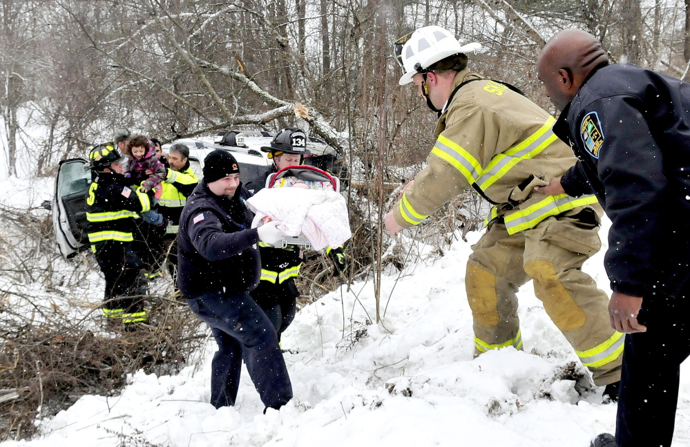Skowhegan police and firefighters pass one of two infants up an embankment after  the car they were riding in that slid off the Norridgewock Road in Skowhegan on Monday. Two other older children also escaped the crash apparently unhurt.