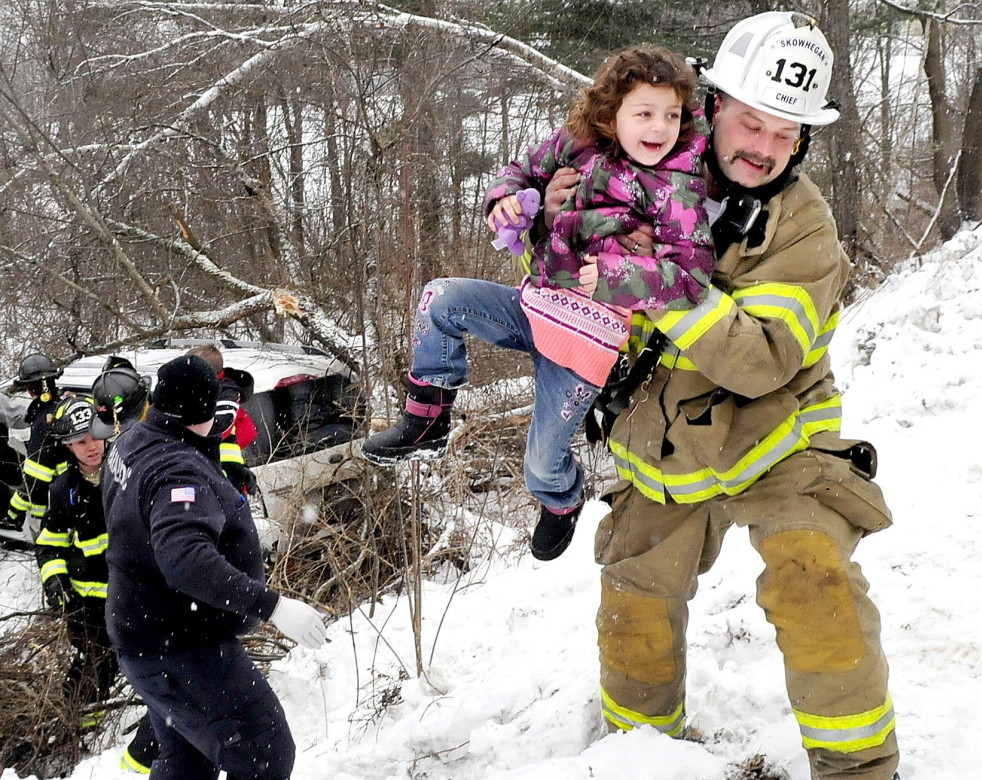 Skowhegan Fire Chief Shawn Howard  carries a young girl who survived the crash when the vehicle in which she and three other children and an adult driver were riding slid off Norridgewock Road in Skowhegan and went down a ravine and struck a tree in January 2015.  The photo won first place for a spot news photo in the Maine Press Association's 2015 contest.
