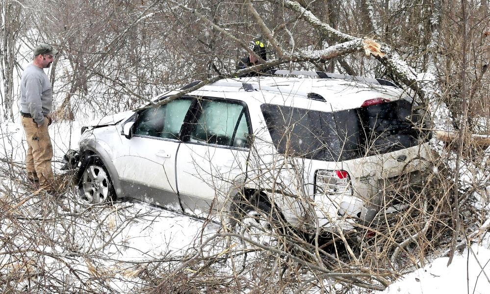 A Skowhegan firefighter, background,  looks inside the vehicle that slid off the snow-covered Norridgewock Road and went down a ravine and struck a tree with the driver and four young children inside on Monday