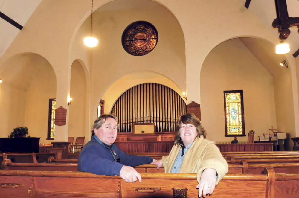 Tom and Stacy O'Brien sit in one of the pews before the front altar of the Madison Congregational Church on Monday. The O'Briens have acquired the historic downtown landmark and plan to turn it into a wedding and event venue called the Somerset Abbey.