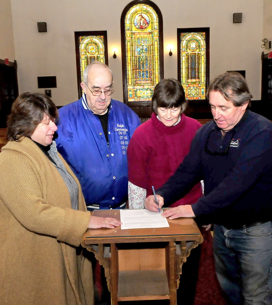 Tom O'Brien, right, signs a deed for the Madison Congregational Church in Madison on Monday. Looking on is his wife Stacy, left, and church members Ralph Withee and Elizabeth Coro. The O'Briens plan to turn the church into a wedding and event venue called the Somerset Abbey.