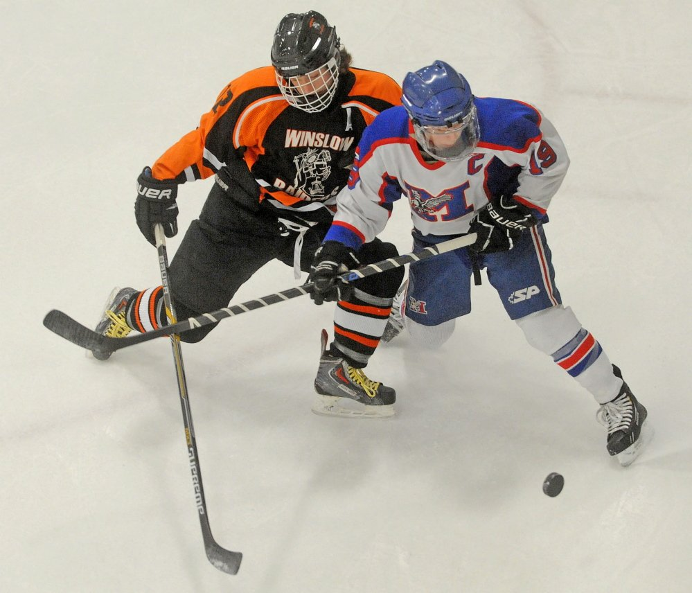 Messalonskee High School's Jared Cunningham (19) battles for the puck with Winslow High School's, Jake Larson (12) in the first period Saturday at Sukee Arena in Winslow.
