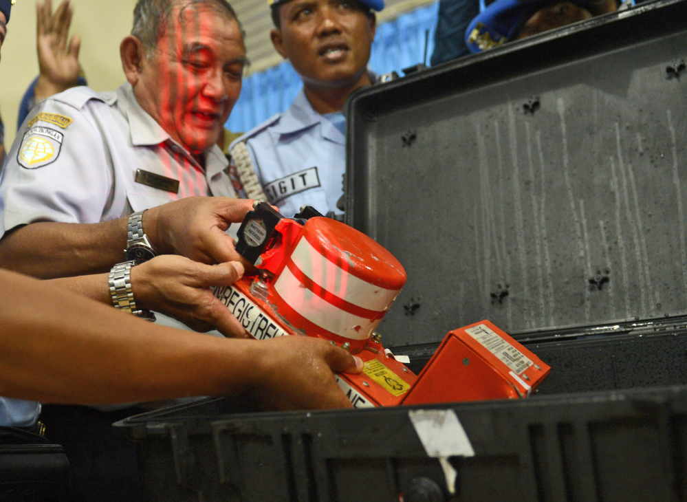 Head of Indonesian National Transportation Safety Committee Tatang Kurniadi, center, shows, the newly recovered Cockpit Voice Recorder from the ill-fated AirAsia Flight 8501 during a press conference in Pangkalan Bun, Central Borneo, Indonesia, Tuesday.