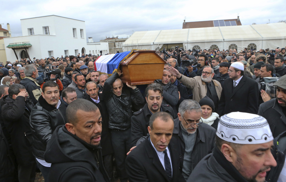People carry the coffin of slain police officer Ahmed Merabet after a funeral service at the  Bobigny mosque, east of Paris, France, Tuesday.