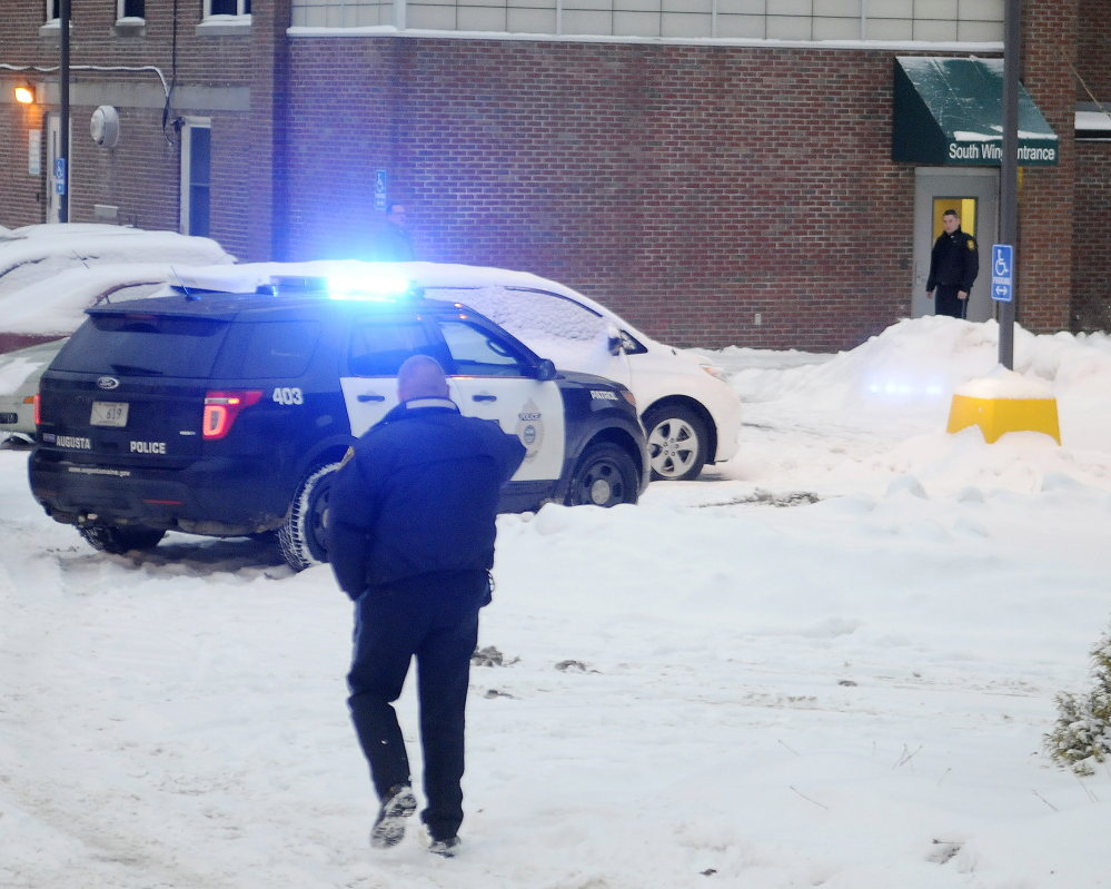 Police approach an entrance of the former MaineGeneral Medical Center in Augusta on Monday a few minutes after an officer-involved shooting in an office in the building.