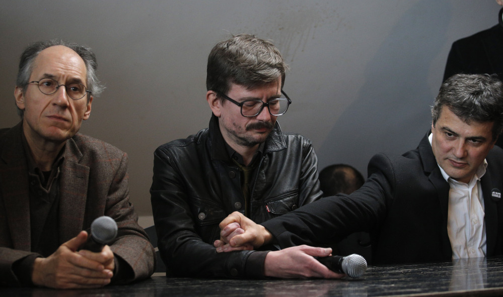The new chief editor of French satirical magazine Charlie Hebdo, Gerard Biard, left, and columnist Patrick Pelloux, right, comfort Cartoonist Renald Luzier, known as Luz  during a press conference in Paris, France, Tuesday.