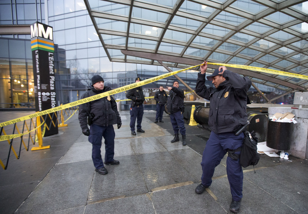 Officers secure the entrance to L'Enfant Plaza Station in Washington, Monday, following an evacuation.