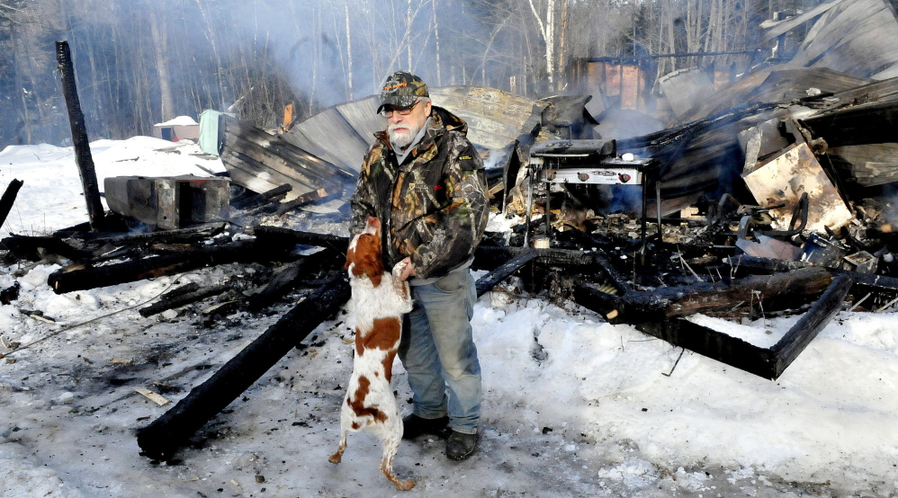 Homeowner Herb Hingley's dog Babe jumps up on him beside his home that was destroyed by fire on the Rowe Pond Road in Pleasant Ridge on Wednesday. Hingley credited his dog with jumping on him and alerting him to the early morning fire.