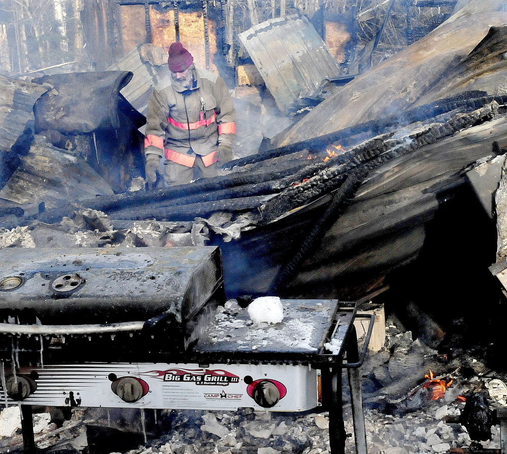 Pleasant Ridge firefighter Stanley Giguere walks through the smokey and burning remains of a home that was destroyed by fire early Wednesday morning in Pleasant Ridge.