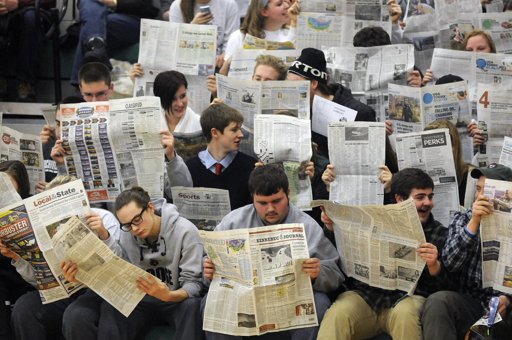 Winthrop High School fans read the newspaper while waiting for Boothbay to complete a foul shot during a Mountain Valley Conference game in January 2015 in Winthrop.