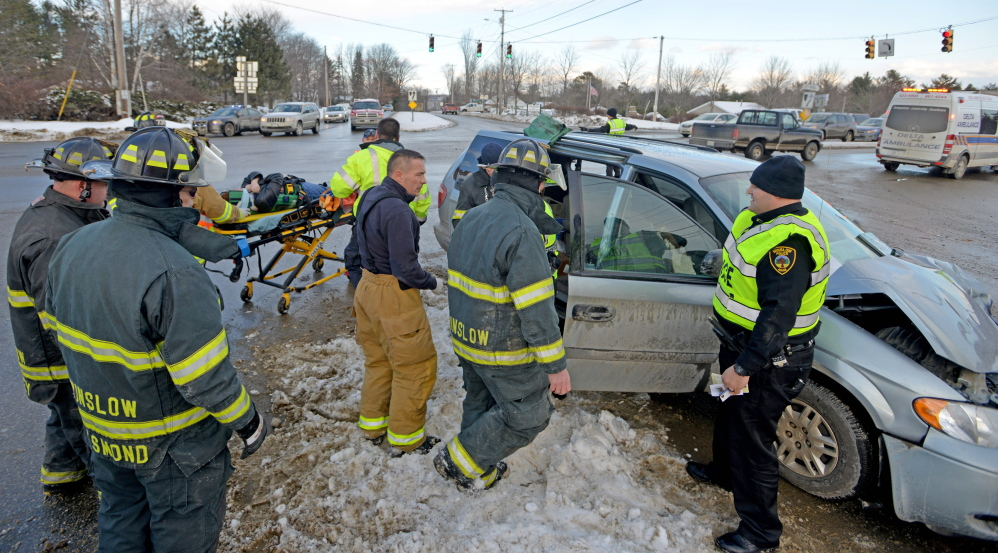 Delta Ambulance paramedics and Winslow firefighters remove a woman from a minivan in which she was a passenger when the van was involved in a three-car accident Friday at the intersection of Carter Memorial Drive and Augusta Road in Winslow.