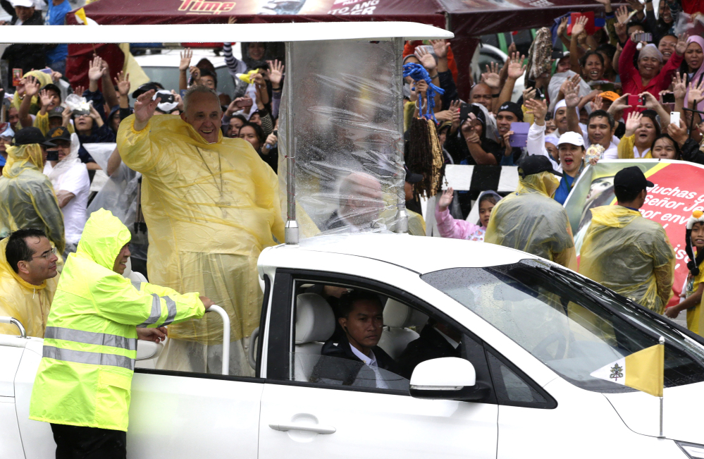Pope Francis waves as he leaves Tacloban, Philippines, on Saturday. Francis cut short his day trip to ground zero of the devastating 2013 Typhoon Haiyan to avoid another approaching storm, but not before consoling survivors at a rain-drenched outdoor Mass.