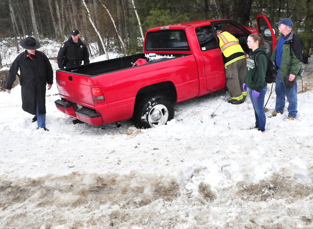 Paramedics lean into this truck to treat the driver after the vehicle went off Route 139 in Benton during freezing rain storm on Sunday.