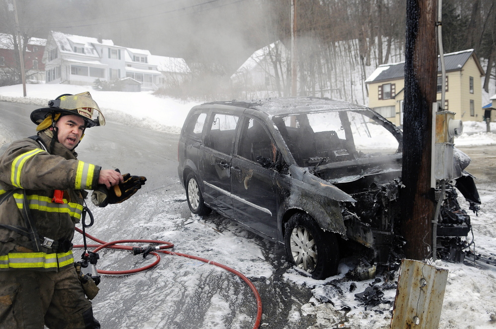 Hallowell firefighter Roy Girard directs fellow volunteers Sunday while extinguishing a van that burned after sliding into a utility pole on Greenville Street in Hallowell. Multiple accidents were reported across central Maine as a light drizzle fell as temperatures remained in the low 30s. The operator of the van had departed by the time firefighters arrived, according to Captain Richard Clark.