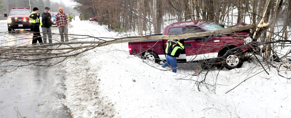 A man retrieves belongings from a pickup truck that slid off ice-covered Route 139 in Fairfield and snapped several trees early Sunday afternoon.