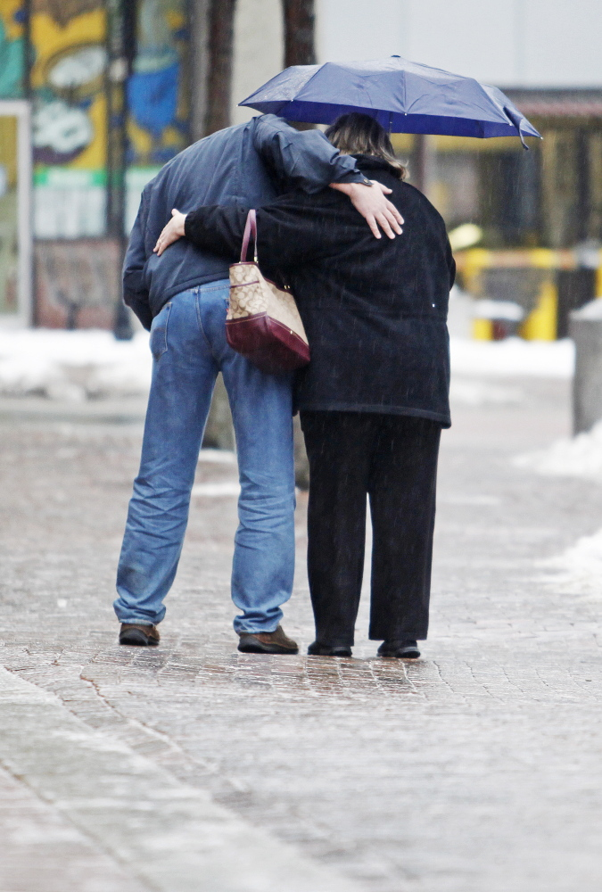Jill Brady/Staff Photographer A couple holds on while making their way gingerly across icy brick sidewalks along Free Street in Portland as a cold rain falls Sunday.