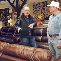 "John Hamelin, left, of Hamelin's Furniture in Waterville speaks with customer Brian Whitney on Thursday. Hamelin said he's ""guardedly optimistic"" about the future of his business."