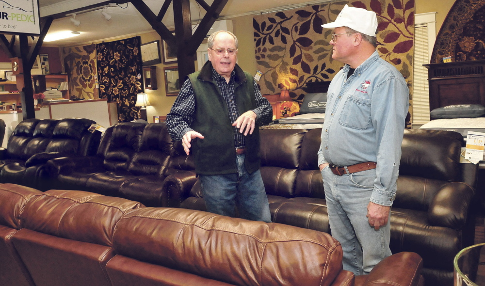 """John Hamelin, left, of Hamelin's Furniture in Waterville speaks with customer Brian Whitney on Thursday. Hamelin said he's """"guardedly optimistic"""" about the future of his business."""