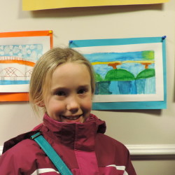 Sophia Wells stands beside her watercolor painting of the Maine Kennebec Bridge.
