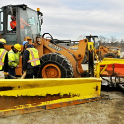 Workers swap from a scoop bucket to plow blades on front end loaders on Friday at the The John Charest Public Works Facility in Augusta.
