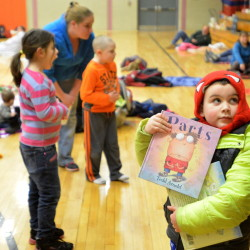 Benjamin Thomas, 5, clutches his favorite books as he arrives at the Books and Blankets event at Winslow Elementary School this week.