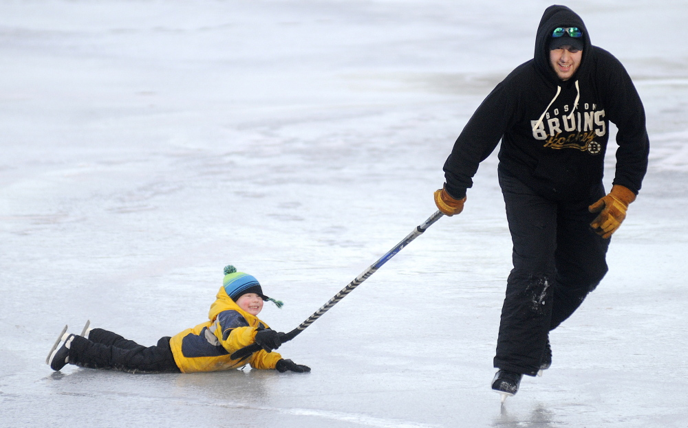 Aiden Lucas, 3, hitches a ride on a hockey stick pulled by his father, Matt, across Lake Cobbossee in Manchester, in between monitoring their ice fishing traps in January 2015. The Augusta residents caught one pickerel.