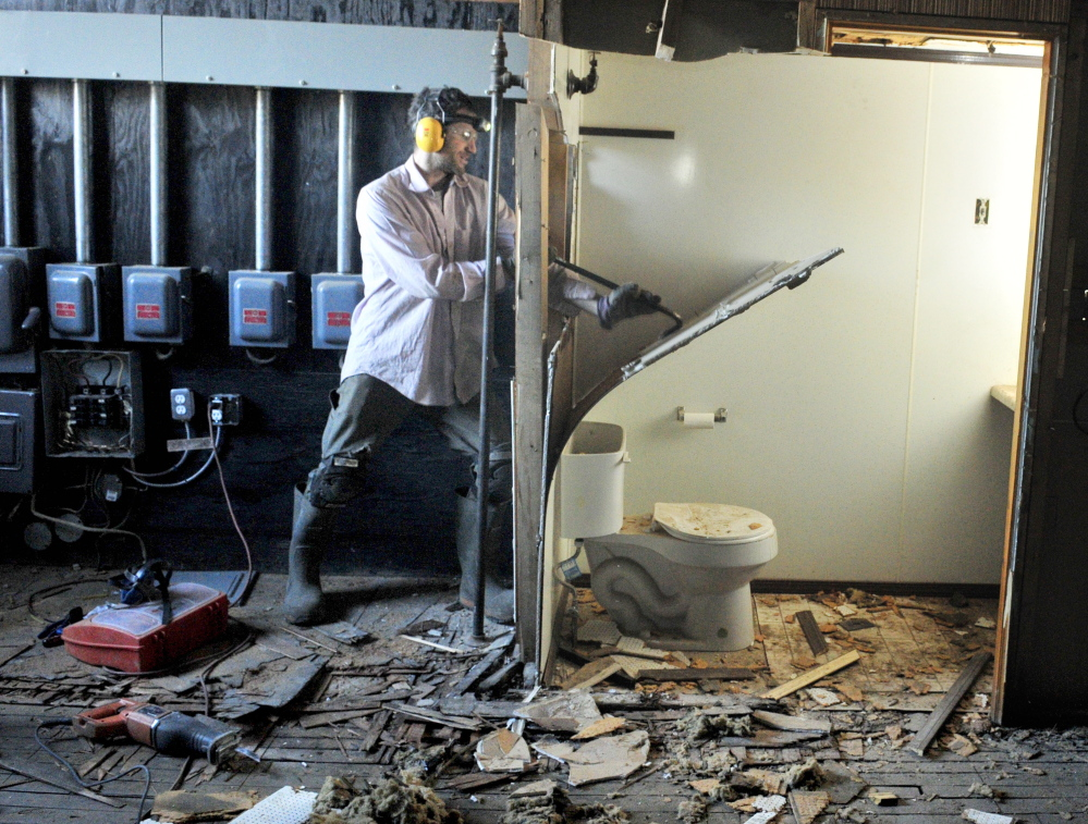 Alex Rosenberg performs demolition work Tuesday in the space that will become the Gardiner Food Co-op & Cafe on Water Street in downtown Gardiner.