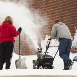 Saco Middle School custodians Lodel Seneres, Joi MacDonald and Donna Jose, clear snow from Saturday's storm on Sunday. They will have more work ahead as a nor'easter is expected to dump at least a foot of snow Monday night through Wednesday morning.