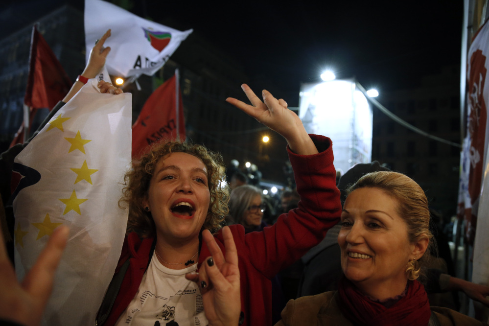 Supporters of left-wing Syriza party react after exit poll results in Athens, on Sunday. The anti-bailout Syriza party won a decisive victory in Greece's national elections, according to projections by state-run TV's exit poll, in a historic first for a radical left-wing party in Greece.