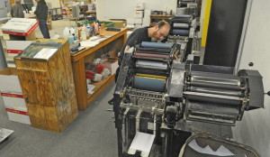 Pressman Kris Soiett cleans an offset press on Wednesday at the Copy Center's new location in Winthrop.