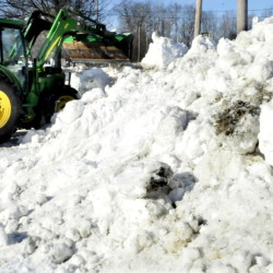 In anticipation of Tuesday's storm, Mark Tyler uses a bucket loader to move snow on Monday to make room for more snow.