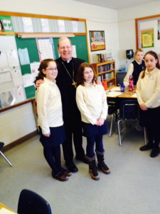 Plain Text:Bishop Robert Deeley meets with sixth grade student Dorothy Anne Giroux-Pare and Julia Bard during a visit to St. John Regional Catholic School in Winslow on Monday.