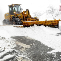 A Waterville Public Works grader clears the nearly deserted Main Street in Waterville on Tuesday.