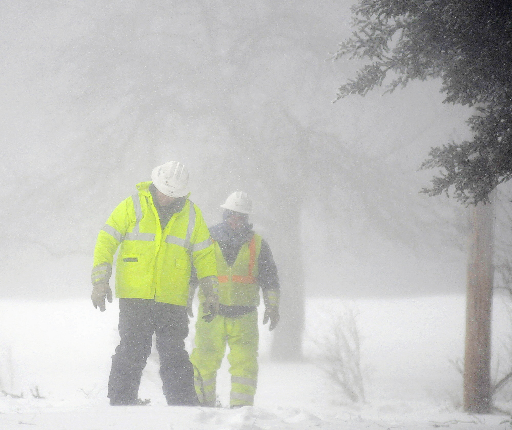 Central Maine Power linemen Sam Pottle, left, and Wayne Piper prepare Tuesday to saw down a tree while restoring electric service to a residence in Hallowell. Piper and Pottle cut down trees and repaired wires in gusts up to 30 miles-per-hour in whiteout conditions.
